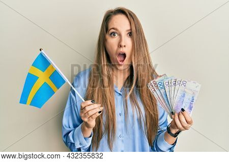 Young blonde woman holding sweden flag and krone banknotes afraid and shocked with surprise and amazed expression, fear and excited face.