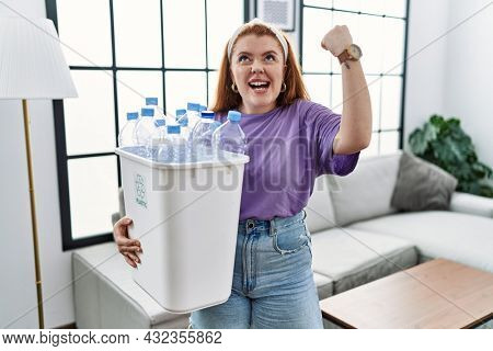 Young redhead woman holding recycling wastebasket with plastic bottles angry and mad raising fist frustrated and furious while shouting with anger. rage and aggressive concept.