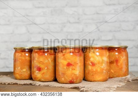 Canned Slices Of Zucchini With Vegetables In Glass Jars, On A Wooden Table. Preparations For The Win