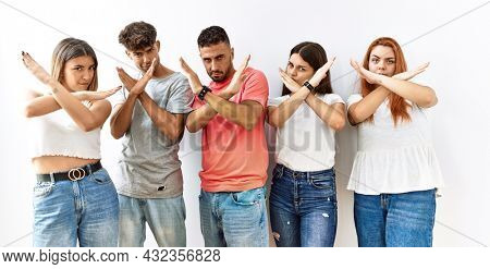Group of young friends standing together over isolated background rejection expression crossing arms doing negative sign, angry face