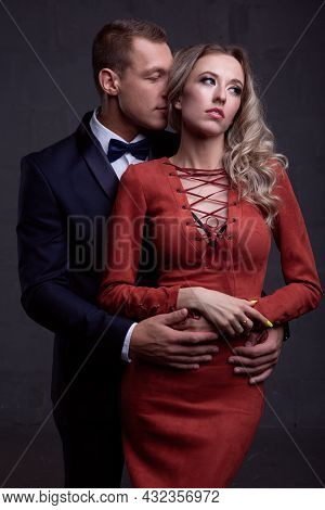 Sexy Elegant Couple In Love In Evening Dresses On A Dark Background