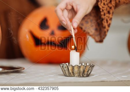 Holidays And Leisure Concept - Woman's Hand With Matches Lighting Candles At Home On Halloween. Pain