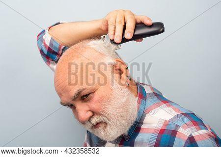 Bearded Man Cutting His Own Hair With A Clipper. Man Hair Treatment. Gray Man Hair Clippings. Bald M