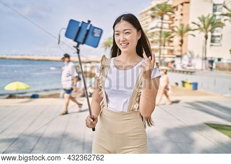Young chinese girl smiling happy having video call using smartphone at the promenade.