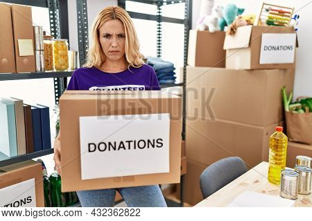 Beautiful blonde woman volunteer holding donations box skeptic and nervous, frowning upset because of problem. negative person.