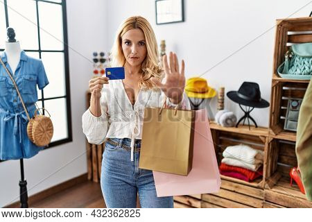 Beautiful blonde woman at retail shop holding credit card with open hand doing stop sign with serious and confident expression, defense gesture