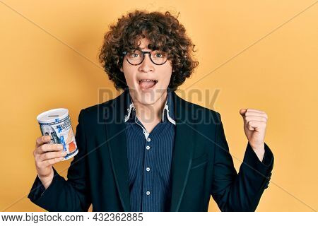 Handsome young man holding piggy bank screaming proud, celebrating victory and success very excited with raised arms