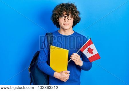 Handsome young man exchange student holding canada flag smiling looking to the side and staring away thinking.
