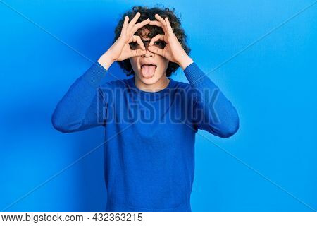 Handsome young man wearing casual clothes and glasses doing ok gesture like binoculars sticking tongue out, eyes looking through fingers. crazy expression.