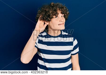 Handsome young man wearing casual striped t shirt smiling with hand over ear listening an hearing to rumor or gossip. deafness concept.