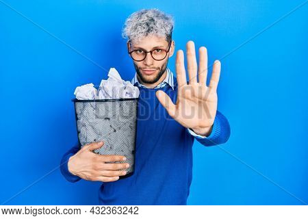 Young hispanic man with modern dyed hair holding paper bin full of crumpled papers with open hand doing stop sign with serious and confident expression, defense gesture