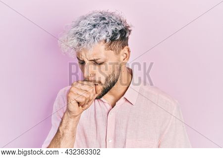 Young hispanic man with modern dyed hair wearing casual pink shirt feeling unwell and coughing as symptom for cold or bronchitis. health care concept.