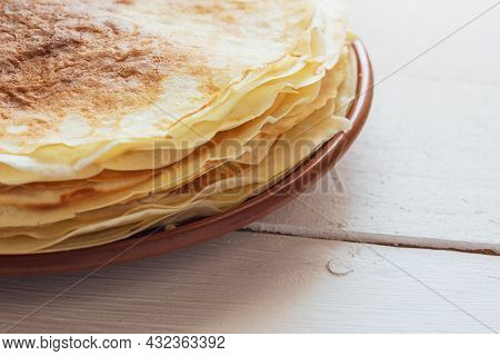 Crepes, Thin Pancakes On A Plate On A White Wooden Table.