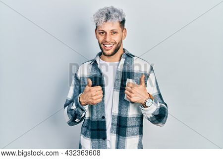 Young hispanic man with modern dyed hair wearing casual shirt success sign doing positive gesture with hand, thumbs up smiling and happy. cheerful expression and winner gesture.