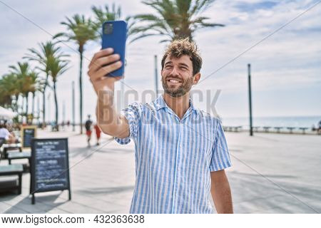 Young hispanic man smiling happy standing at the promenade.