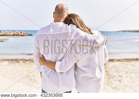 Middle age hispanic couple of husband and wife together walking by the beach on a sunny day. Hugging in love on vacation to the seaside.