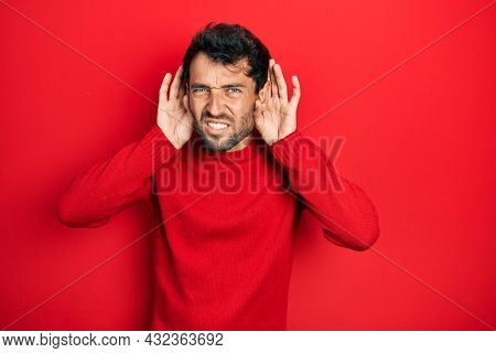 Handsome man with beard wearing casual red sweater trying to hear both hands on ear gesture, curious for gossip. hearing problem, deaf
