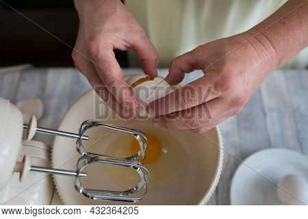 Cake Making Process. Female Hands Add Eggs To The Mixer Bowl For Making Dough. Step By Step Recipe F