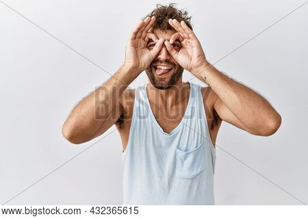 Young handsome man standing over isolated background doing ok gesture like binoculars sticking tongue out, eyes looking through fingers. crazy expression.