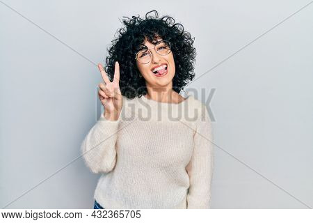 Young middle east woman wearing casual white tshirt smiling with happy face winking at the camera doing victory sign. number two.