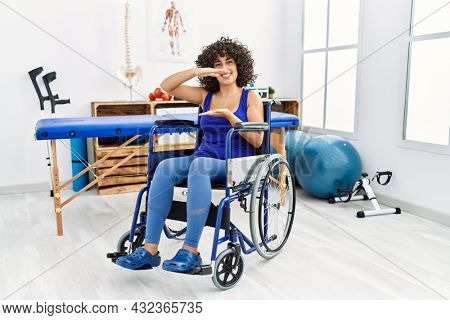Young middle eastern woman sitting on wheelchair at physiotherapy clinic gesturing with hands showing big and large size sign, measure symbol. smiling looking at the camera. measuring concept.