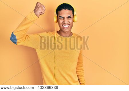 Young african american guy listening to music using headphones angry and mad raising fist frustrated and furious while shouting with anger. rage and aggressive concept.