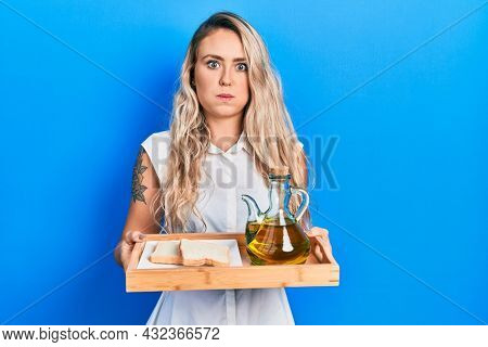 Beautiful young blonde woman holding tray with olive oil and bread toast puffing cheeks with funny face. mouth inflated with air, catching air.
