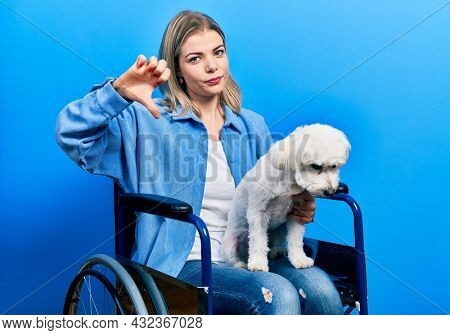 Beautiful caucasian woman sitting on wheelchair hugging dog with angry face, negative sign showing dislike with thumbs down, rejection concept