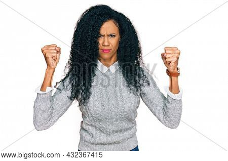 Middle age african american woman wearing casual clothes angry and mad raising fists frustrated and furious while shouting with anger. rage and aggressive concept.