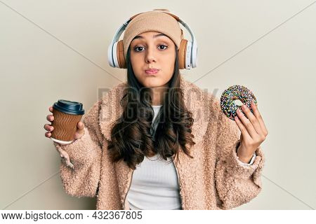 Young hispanic woman using headphones having breakfast puffing cheeks with funny face. mouth inflated with air, catching air.
