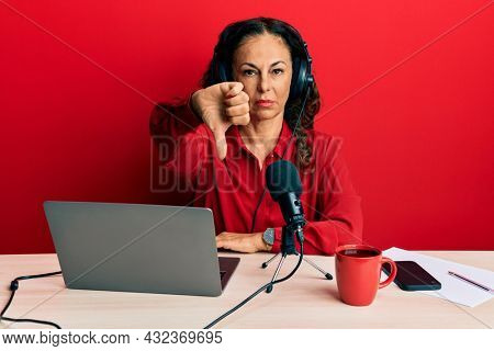 Beautiful middle age woman working at radio studio looking unhappy and angry showing rejection and negative with thumbs down gesture. bad expression.