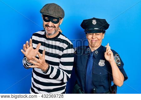 Middle age couple of hispanic woman and man wearing thief and police uniform gesturing finger crossed smiling with hope and eyes closed. luck and superstitious concept.