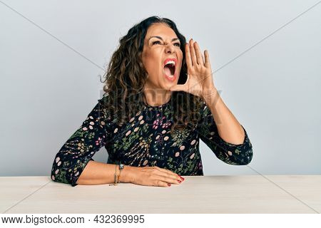 Beautiful middle age woman wearing casual clothes sitting on the table shouting and screaming loud to side with hand on mouth. communication concept.