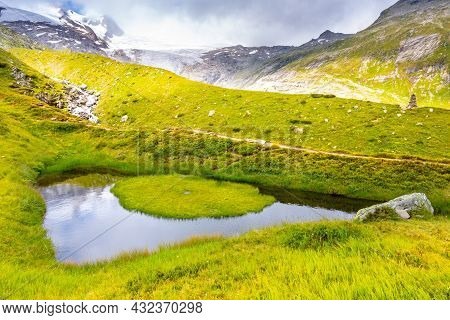 Eye Of God, German: Auge Gottes. Small Mountain Lake With Tiny Green Island In Venediger Group, Hohe