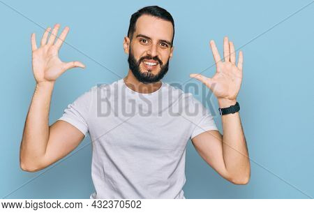 Young man with beard wearing casual white t shirt showing and pointing up with fingers number ten while smiling confident and happy.