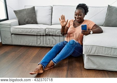 Young african woman using smartphone sitting on the floor at home waiving saying hello happy and smiling, friendly welcome gesture