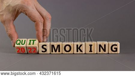 Quit Smoking 2022 New Years Resolution Symbol. Businessman Turns Wooden Cubes With Words '2022 Quit
