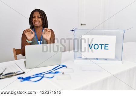 Young african american woman working at political election sitting by ballot disgusted expression, displeased and fearful doing disgust face because aversion reaction.