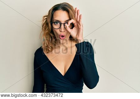 Young caucasian woman wearing business shirt and glasses doing ok gesture shocked with surprised face, eye looking through fingers. unbelieving expression.