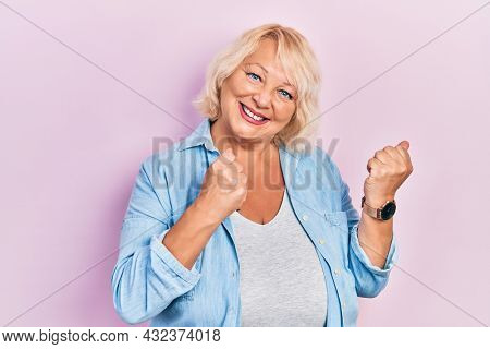 Middle age blonde woman wearing casual clothes excited for success with arms raised and eyes closed celebrating victory smiling. winner concept.