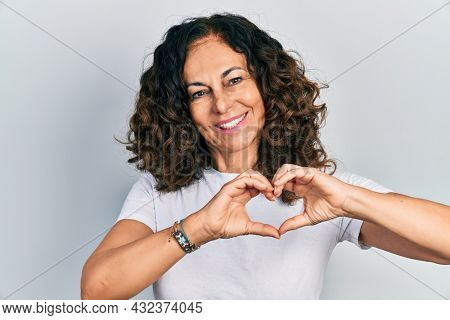 Middle age hispanic woman wearing casual white t shirt smiling in love doing heart symbol shape with hands. romantic concept.