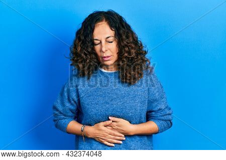 Middle age hispanic woman wearing casual clothes with hand on stomach because indigestion, painful illness feeling unwell. ache concept.