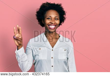African american woman with afro hair wearing casual white t shirt showing and pointing up with fingers number three while smiling confident and happy.
