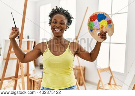 Young african american artist woman smiling happy drawing at art studio.