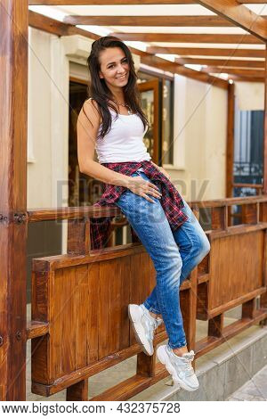 Young Caucasian Woman Is Smiling Standing On Porch Near Door Of Store In Casual Clothes. Pretty Woma