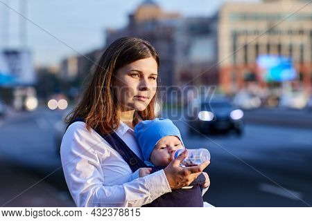 Young Woman Gives Drink To Baby In Sling On Street.
