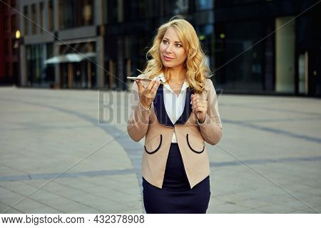 Attractive Woman In Business Suit Talking On Phone In Front Of Office Building.