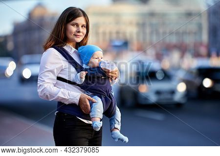 Young Mother Uses Baby Sling For An Outdoor Walk With Her Child.