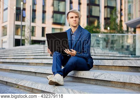 An Office Worker With Laptop On His Knees Sits On Step In Front Of Building Of Business Center.