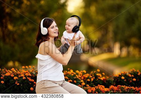 Wireless Headphones For Young Woman And Her Baby During Walk In Nature On Summer Evening.